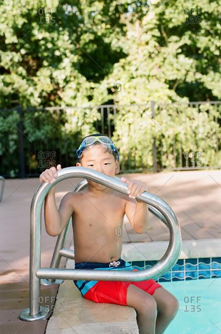 Boy sitting at pool ladder