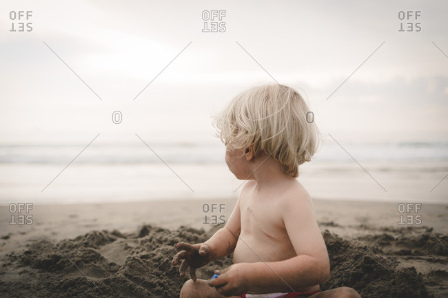 Little boy playing in sand on beach looking at waves