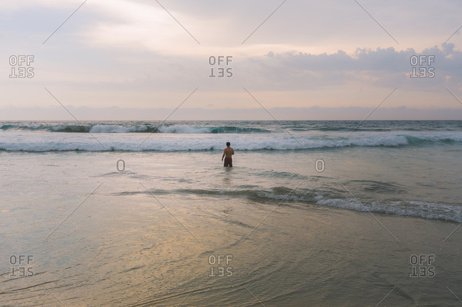 Man wading in ocean waves