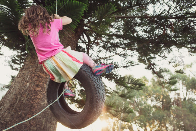Girl swinging high on tire swing from tree