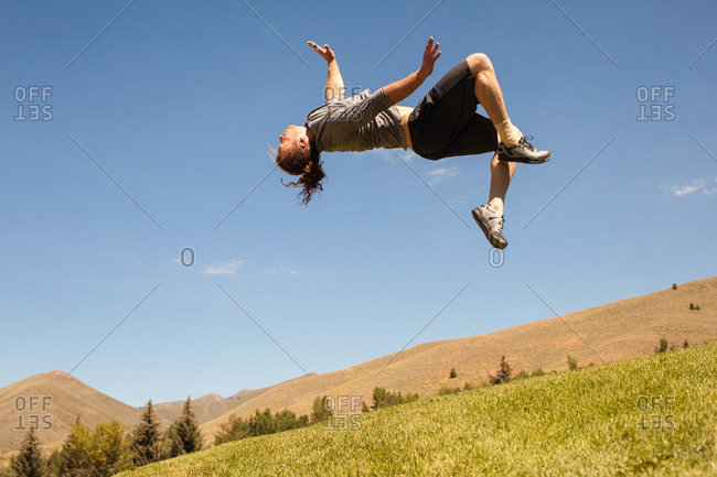Young athletic man doing back flip outdoors