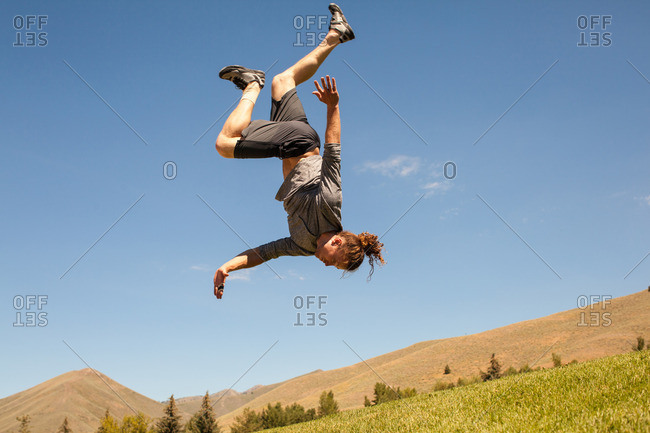 Young athletic man doing flips outdoors