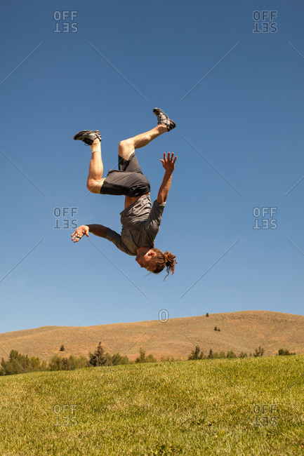 Athletic man doing back flip outdoors