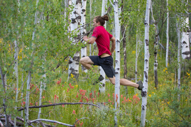 Young athletic man sprinting through the woods
