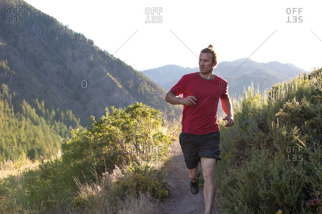 Young athletic man jogging on a rural path