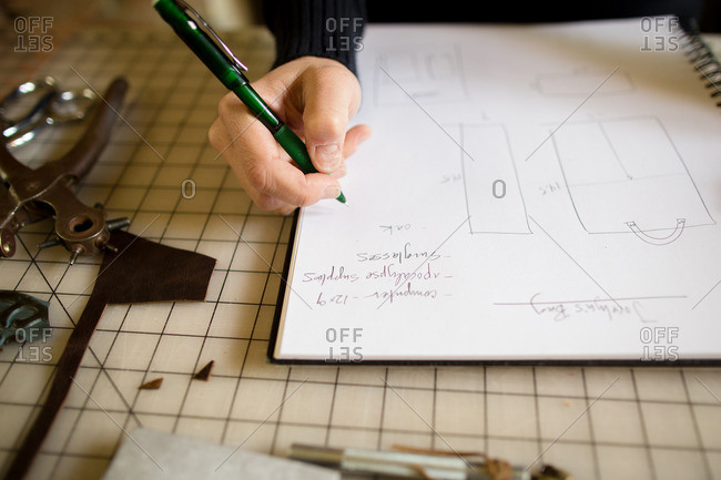 Woman drawing leather accessory ideas