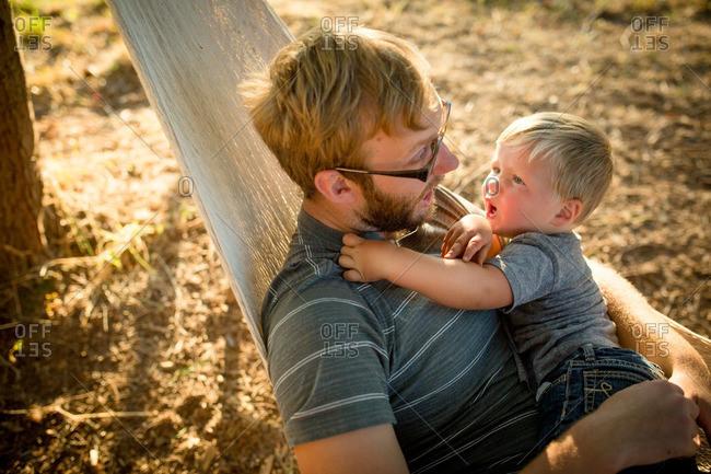 Surprised boy and dad in hammock