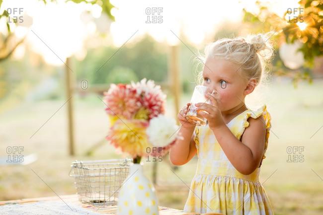 Sun dappled girl drinking from glass