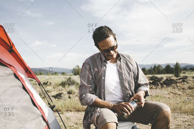 Man opening tin can while camping