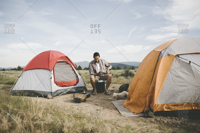 Man using cell phone while camping
