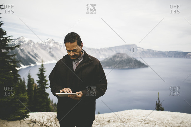 Man using tablet at Crater Lake National Park, Oregon