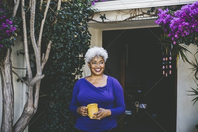 Middle-aged woman standing on her front porch drinking coffee