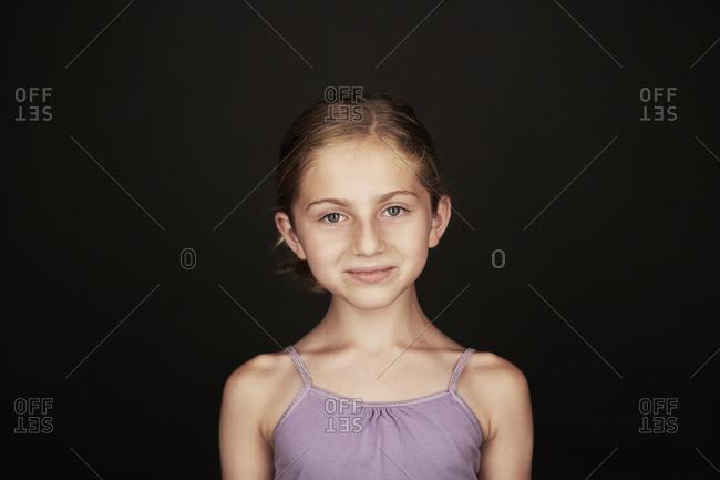 Portrait of a happy little girl wearing a purple tank top