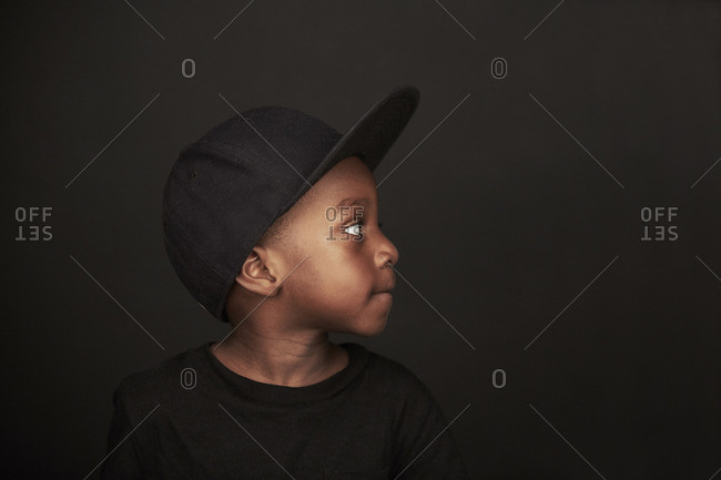 Portrait of a young boy wearing a black hat looking away