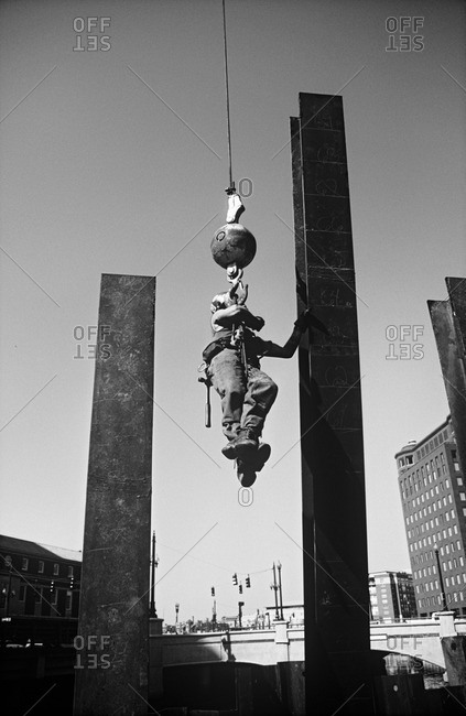 A builder hanging from a crane