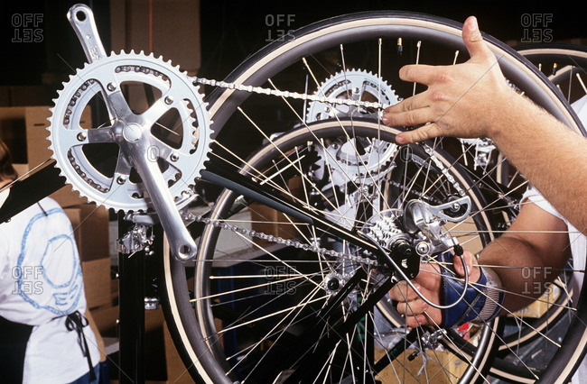 A factory worker checking a bicycle wheel