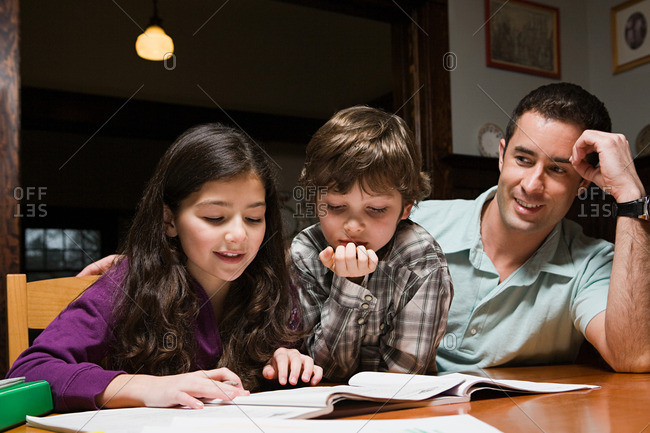 A father supervising his children with their homework