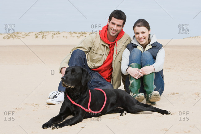 Couple sitting on beach with pet dog
