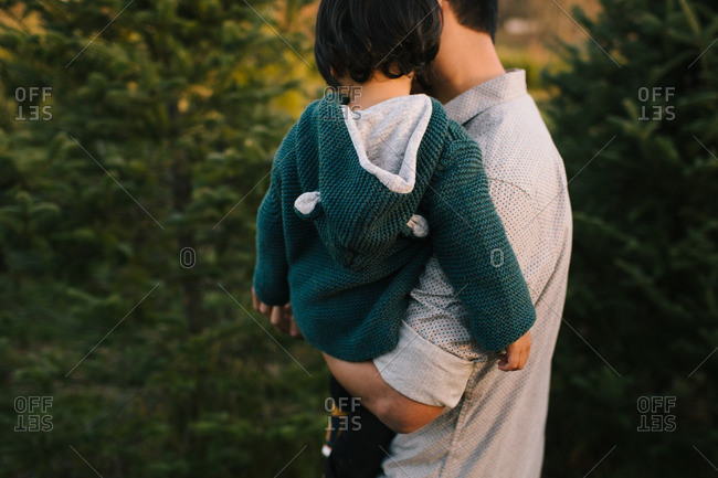 Father holding his child while walking outside in the forest