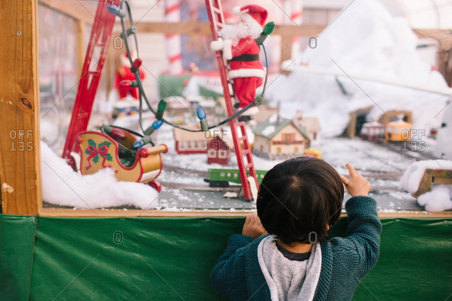 Little boy looking into the window of a toy shop at Christmastime