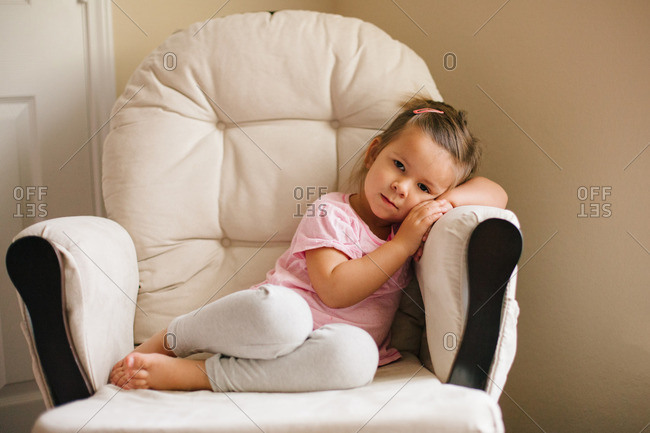 Girl seated in a chair resting her head