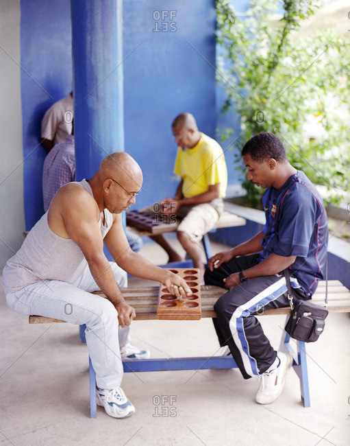 Cape Verde Island , Africa - January 22, 2008: Men sitting on benches playing the game of ouril in Mindelo, Cape Verde Islands