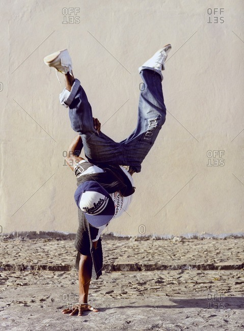Cape Verde Island , Africa - December 9, 2010: Young man performing a one-arm handstand in Sao Felipe, Cape Verde Islands
