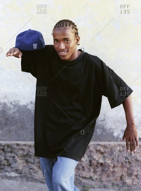 Cape Verde Island , Africa - November 1, 2010: Hip-hop dancer balancing his cap on his shoulder in Sao Felipe, Cape Verde Islands