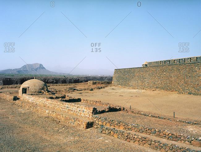 Wall of Sao Filipe fort and distant mountain peak in Ciadade Velha, Cape Verde Islands