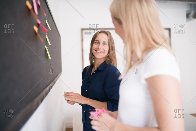 Two young women placing sticky notes on a blackboard