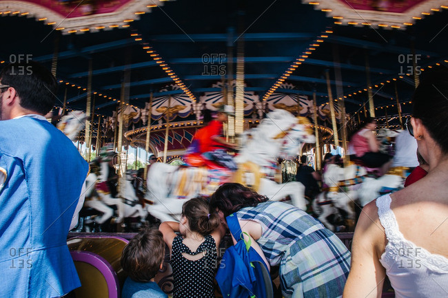 Family standing in front of a carousel watching it spin past