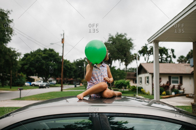 Little girl sitting on the roof of a  car holding a green balloon