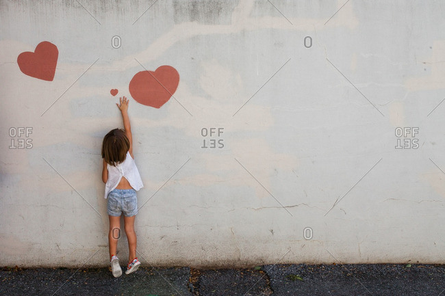 Little girl reaching for hearts painted on a cement wall