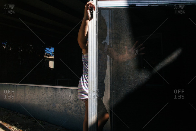 Little girl holding an open screen door