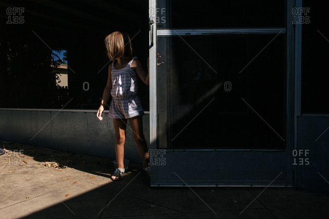 Little girl standing at an open screen door