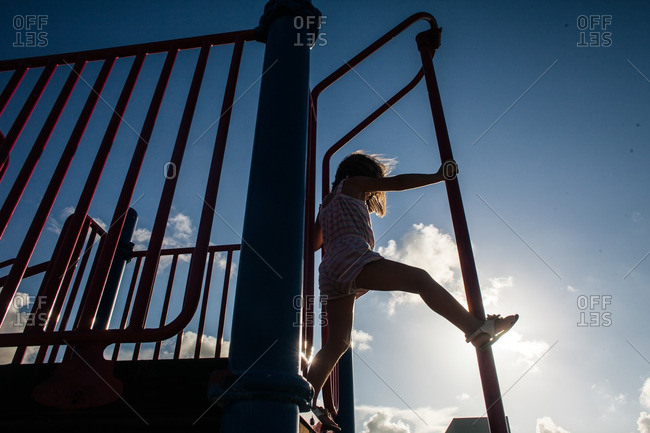 Girl playing on a fireman's pole at a playground