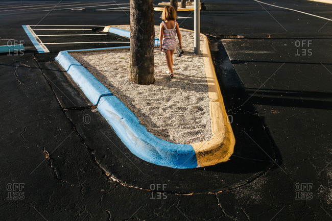Little girl walking in a sandy median in a parking lot