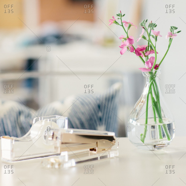 Vase of flowers, tape dispenser and stapler on desk