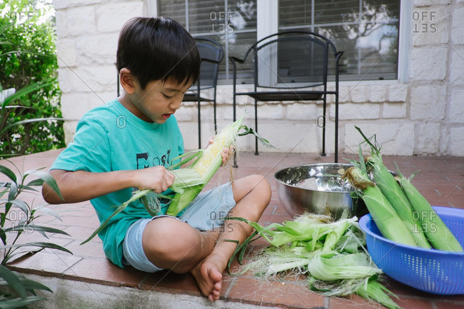 Young boy peeling husk off corn on patio
