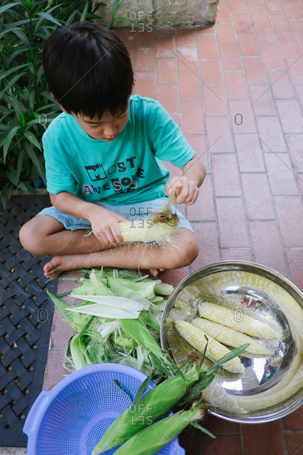 Overhead view of young boy peeling corn on patio