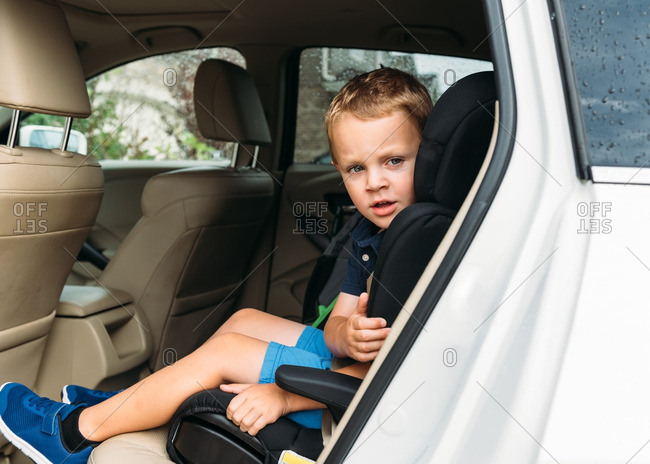 Preschool-aged boy sitting in his car seat in back of car