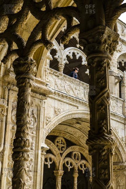 Lisbon Portugal - April 18, 2014: Woman overlooking balcony in Hieronymites Monastery (Mosteiro dos Jeronimos), Lisbon, Portugal