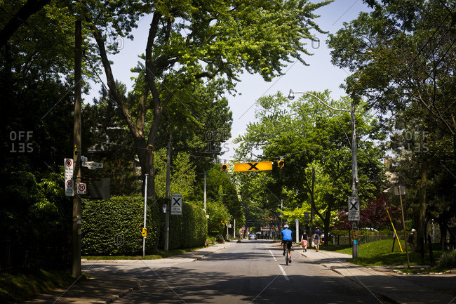 Toronto, Canada - June 23, 2013: A cyclist in a quiet district of Toronto, Canada.