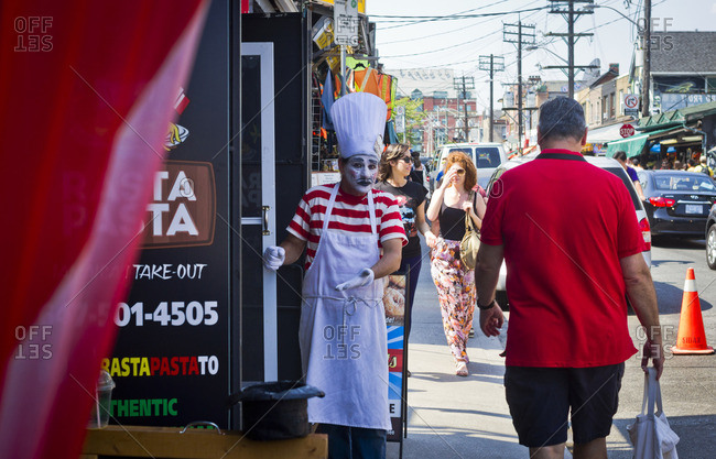 Toronto, Canada - June 24, 2013: A mime tries to attract people into a restaurant in the Kensington area of Toronto, Canada