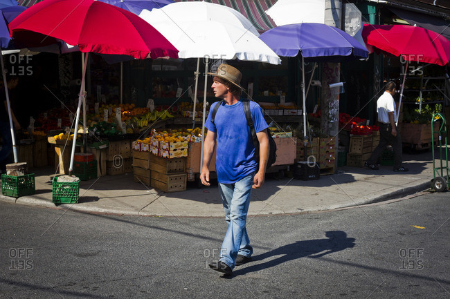 Toronto, Canada - June 24, 2013: A pedestrian walking by a fruit market in the Kensington area of Toronto, Canada
