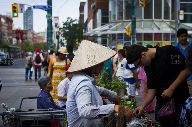 Toronto, Canada - June 24, 2013: A female Vietnamese street vendor wearing conical hat in the Chinatown area of Toronto, Canada