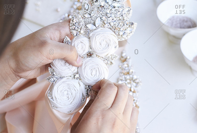 Person applying jewelry to a wedding accessory