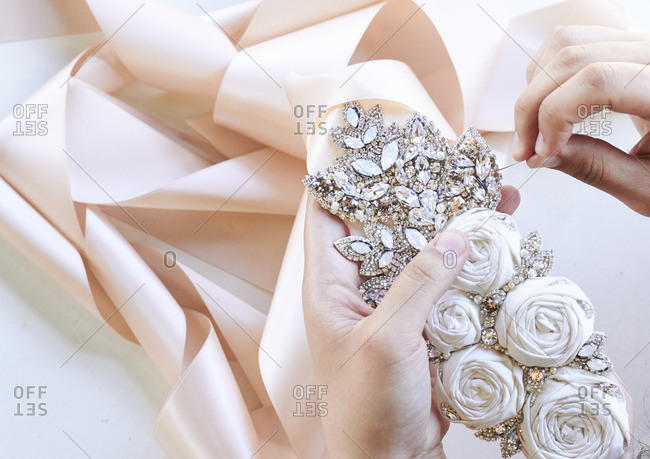 Person sewing a piece onto a wedding accessory
