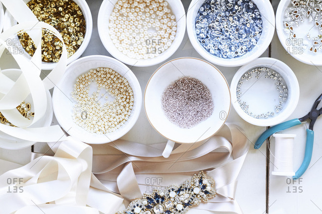 Overhead view of a crafting table covered with bowls of beads, gemstones, and fabric