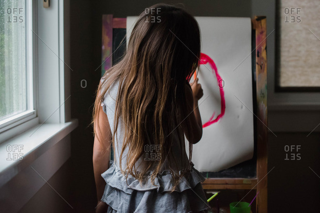Girl painting at easel in home